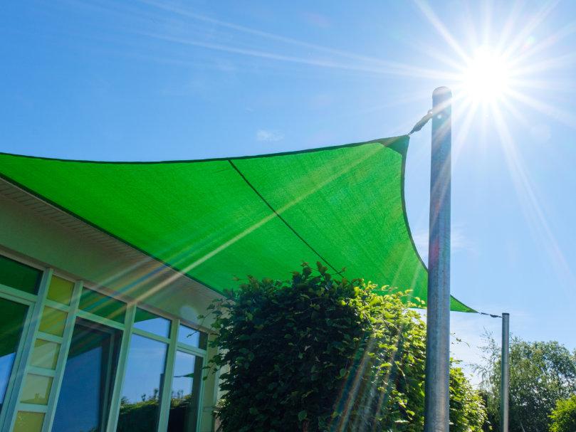Wie befestigt man ein Sonnensegel? Grünes Segel mit Keder am Haus und an zwei Pfosten befestigt